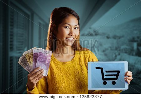 Smiling asian woman showing tablet and bank notes against stylish outdoor patio area