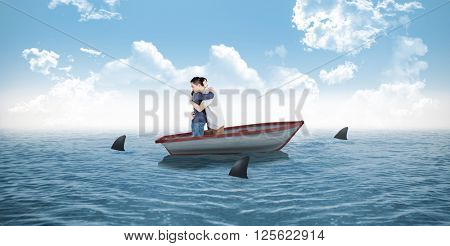 Couple hugging each other against sharks circling small boat in the ocean