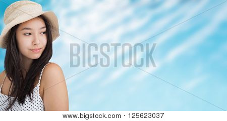 Woman with a straw hat looking away against ripples on blue swimming pool
