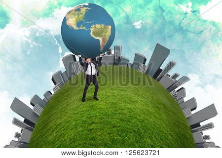 Businessman carrying the world against green and blue sky