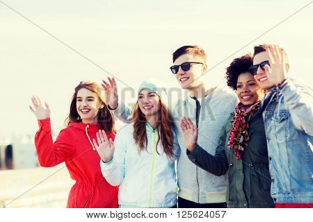 people, friendship, gesture and international concept - happy teenage friends waving hands on outdoors
