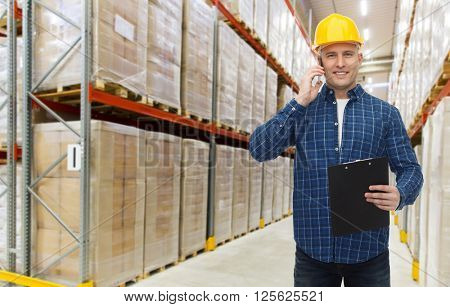 wholesale, logistic, business, export and people concept - smiling businessman with clipboard calling on smartphone over warehouse background