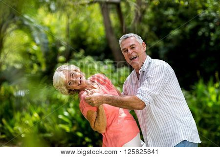 Portrait of senior couple enjoying while dancing in yard