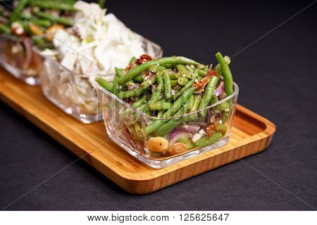 Healthy green beans salad and tasty Waldorf salad served in glass bowls and bamboo tray
