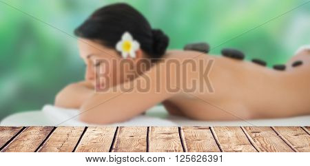 Beautiful brunette relaxing on massage table against wooden table