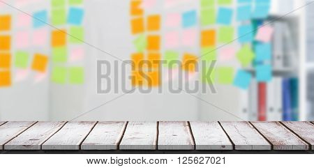 Wooden table against closeup of colorful sticky notes at office
