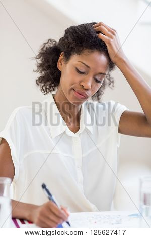 Tense businesswoman writing a report in office