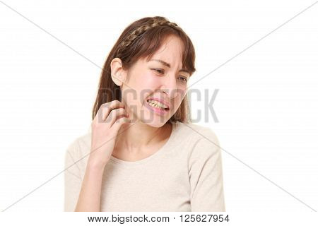 young woman scratching her neck on white background