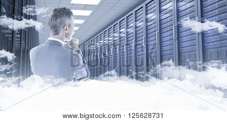 Businessman thinking against server hallway