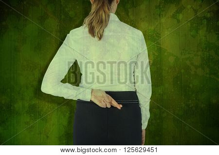 Rear view of businesswoman with fingers crossed over white background against green paint splashed surface