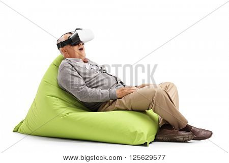 Excited senior looking in a VR headset seated on a green beanbag isolated on white background