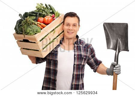 Young farmer holding a shovel and a wooden crate full of fresh vegetables isolated on white background