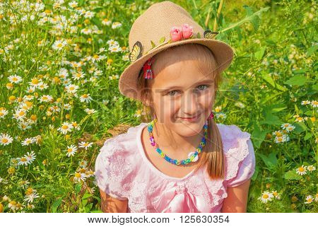 Portrait of a cute little girl in a hat in style of the country