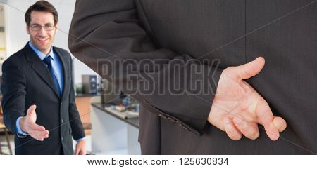 Businessman with fingers crossed against empty chairs by desk with computers