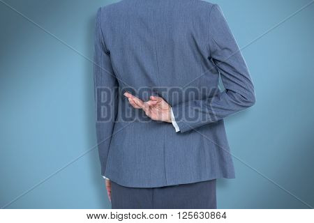 Businesswoman with fingers crossed behind her back against blue
