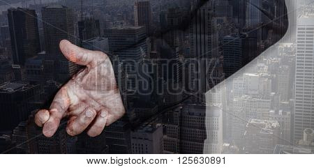 Businessman with fingers crossed against view of cityscape