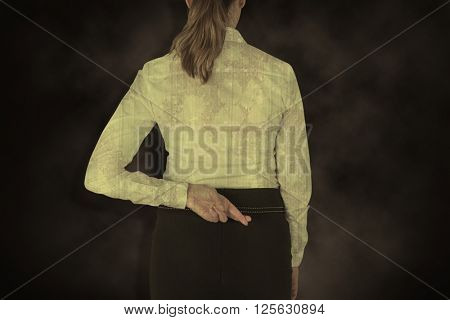 Rear view of businesswoman with fingers crossed over white background against dark background