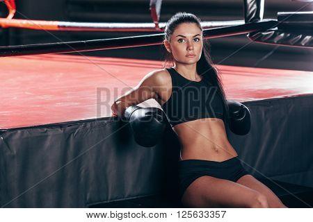 brunette woman wearing black sportwear in boxing gloves sitting near ring