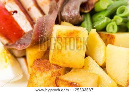 Delicious nicoise salad with anchovies and baked potatoes. Macro. Photo can be used as a whole background.