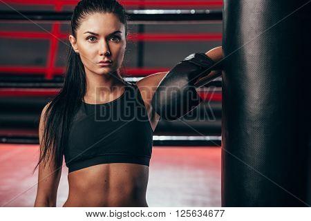 brunette woman wearing black sportwear and boxing gloves posing near puncing bag