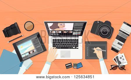 Professional photographer working at office desk he is editing his pictures using a laptop and a graphic tablet
