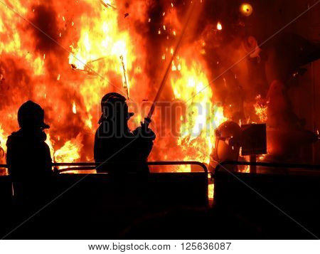 Great Fire of burning figures during the Las Fallas (festival in Spain, Valencia) on the background of two silhouettes of fire fighters