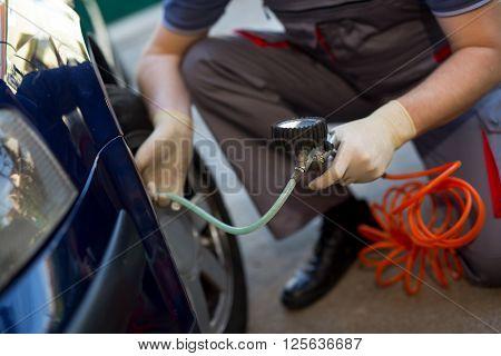 Mechanic repairman at car tyre fitting and balancing adjustment