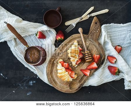 Breakfast set. Freshly baked croissants with strawberries, mascarpone, honey and coffee on rustic wooden board over dark grunge backdrop, top view