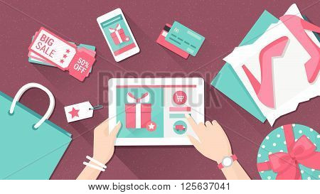 Online shopping and delivery concept woman buying fashion products from an e-shop using a digital touch screen tablet flat lay