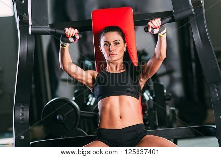caucasian woman exercising on shoulder press machine in gym