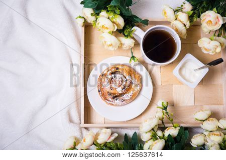 Top View Of Breakfast With Bun, Tea And Yoghurt On Wooden Tray