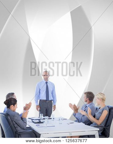 Business people applauding during meeting against white angular design