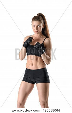 Sporty muscular fitness girl clenching her fists in black gloves in defensive stance with a determined face expression