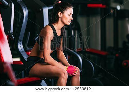 caucasian woman sitting on shoulder press machine in gym