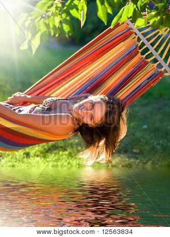 Happy Young Woman relaxing in hammock