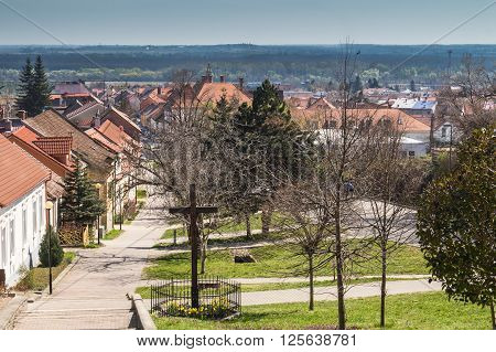 Center of the traditional slovak village built on a hill. Residential houses and bright green grass. View from the top of the hill to the city surrounded by nature.