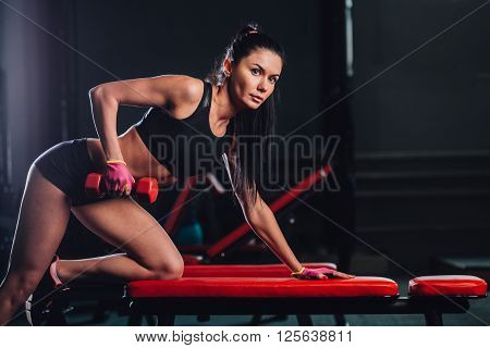 brunette woman exercising red dumbbell row at the gym, copy space