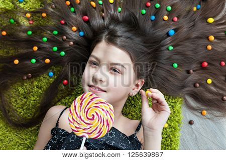 Little girl with dark hair lying on the floor among the sweets. Top view of a big yellow and pink lollipops in hands. Many candies in her hair. the smile, the joy on a child's face.
