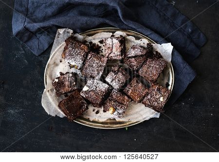 Dark chocolate and walnut brownie squares on a silver tray over black grunge surface, horizontal