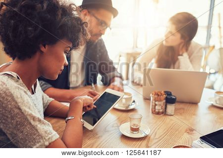 Close up portrait of young african woman using digital tablet with her friends sitting by at a cafe table. Group of young people sitting at a coffee shop with digital tablet and laptop.