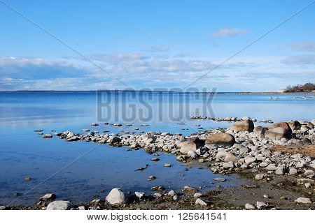 Sunlit stony coastline by a calm bay of the Baltic Sea at the island Oland in Sweden
