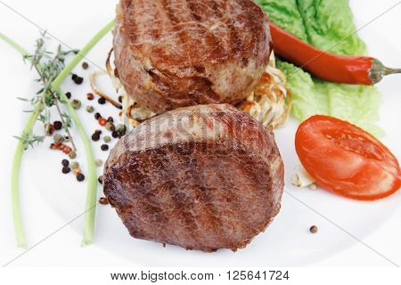 grilled beef fillet with thyme , red hot chili pepper and tomato on plate isolated over white background