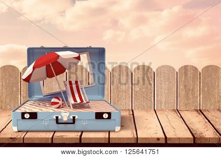Image of a suitcase against purple sky over fence