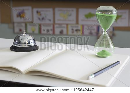 Hourglass with green sand and front desk bell on white notebook with pencil selective focus on hourglass blur foreground and background