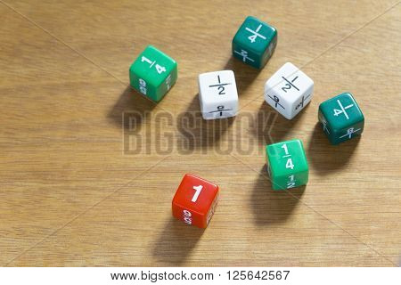 Multiple fraction dices shown in quarters halves and full number set on wood table selective focus on number one