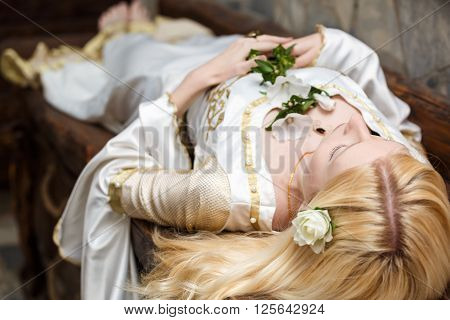 Sleeping beauty lying on the table with flowers