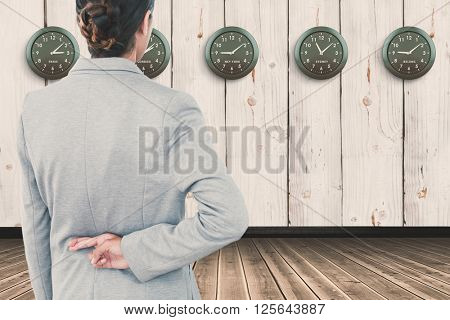 Businesswoman with fingers crossed behind her back over white background against wooden room