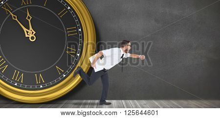 Geeky young businessman running late in front of a clock