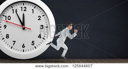 Geeky happy businessman running mid air on a black room and in front of a clock