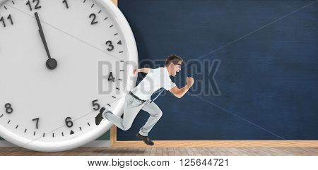 Geeky happy businessman running mid air in front of a clock and chalkboard